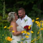 Wedding couple embracing in a field of yellow flowers